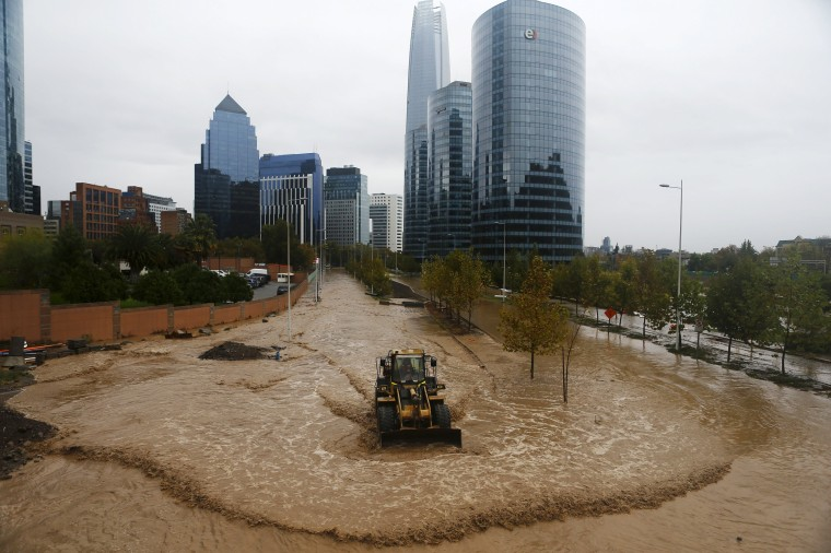 Image: A loader works on a flooded street in Santiago