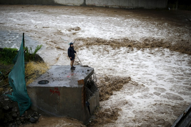 Image: A man is seen next to a river during floods in Santiago