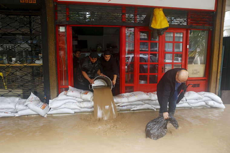 Image: Workers remove water from a store in a flooded street in Santiago