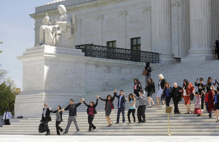 Image: Immigration activists join hands after the U.S. Supreme Court heard arguments over the constitutionality of President Obama's executive action to defer deportation of certain immigrants, in Washington