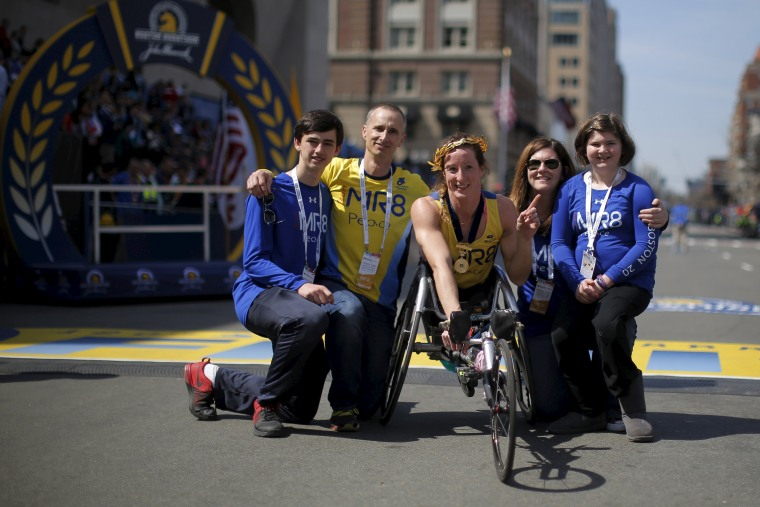 Image: Tatyana McFadden of the U.S. poses for photographs with the family of Boston Marathon bombing victim Martin Richard after winning the women's wheelchair division of the 120th running of the Boston Marathon in Boston, Massachusetts