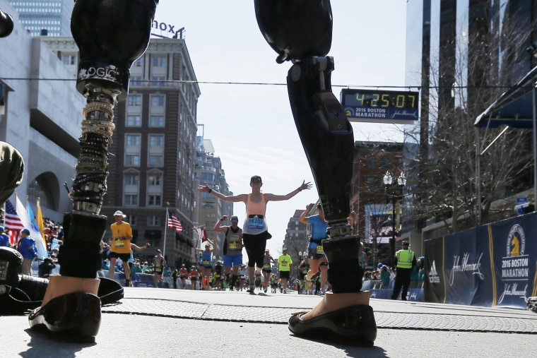 Image: Celeste Corcoran, who lost both her legs in the Boston Marathon bombings, greets runners at they finish the120th running of the Boston Marathon in Boston