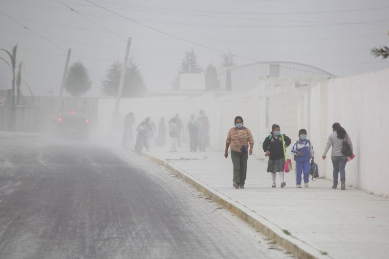 Image: People walk on the ash-covered streets of San Andres Cholla