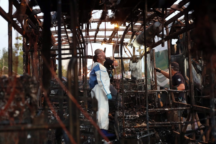 Image: Israeli forensics search in the remains of a burnt-out a bus