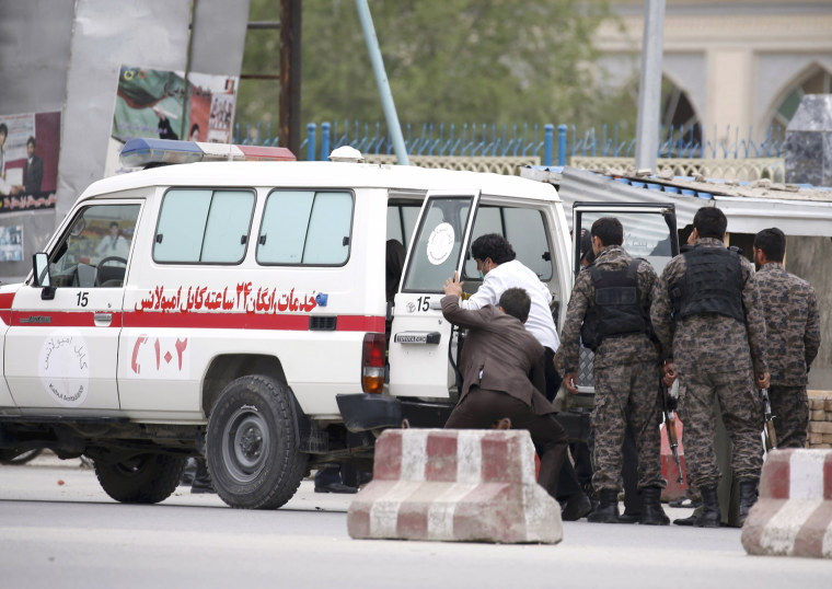 Image: Afghan security forces transfer injured security personnel into an ambulance after a suicide car bomb attack in Kabul