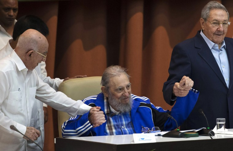 Image: Fidel Castro sits as he clasps hands with his brother