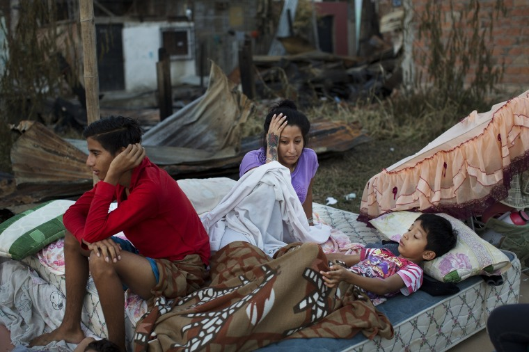 Image: A family wake up after sleeping outside their collapsed home in Manta, Ecuador