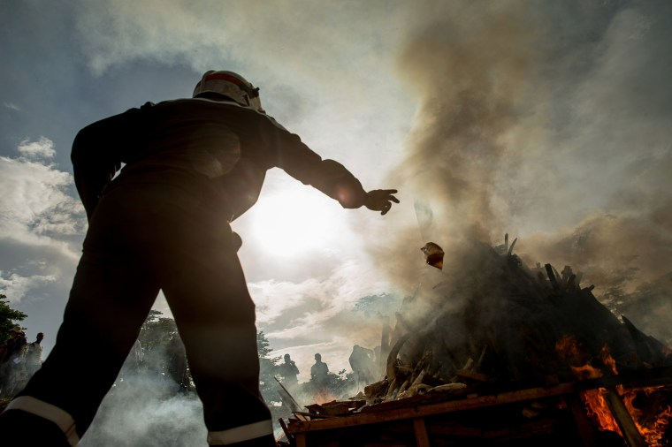 Image: A firefighter throws a plastic bag of accelerant onto the first ever Cameroon Ivory Burn