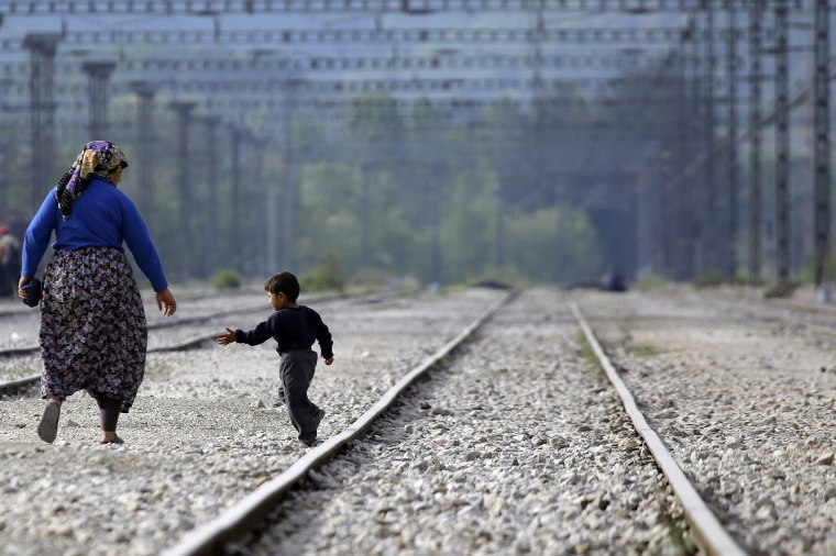 Image: A woman walks with a child along the train tracks near a makeshift camp at the northern Greek border point of Idomeni