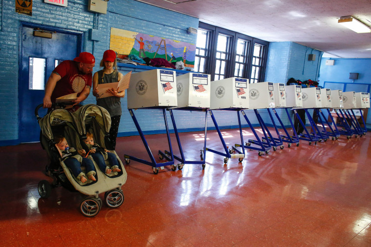 Image: A couple check their documents before they cast their vote