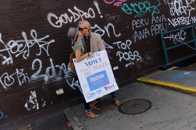 Image: A couple shares a kiss as they hold a sign to promote the vote for Bernie Sanders