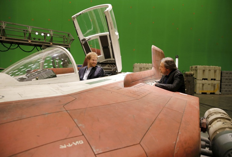 Image: Britain's Prince Harry sits in an A-wing fighter as he talks with US actor Mark Hamill during a tour of the Star Wars sets at Pinewood studios in Iver Heath, west of London