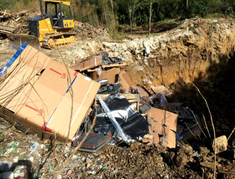 A bulldozer is parked next to a hole in the ground filled with televisions and other electronics in an illegal landfill in Scott County, Kentucky. Global Environmental Service confessed to the illegal dumping.