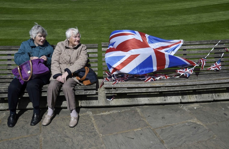 Image: Visitors sit on a bench outside of Windsor Castle in Windsor Britain