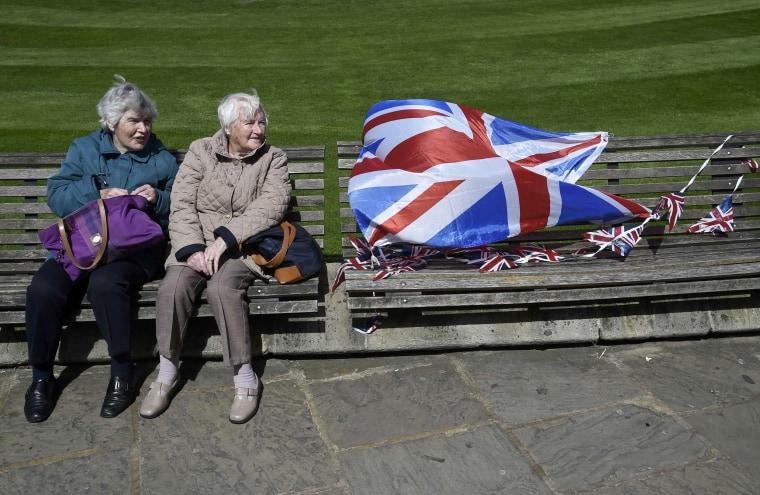 Image: Visitors sit on a bench outside of Windsor Castle in Windsor Britain