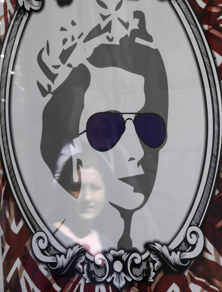 Image: A passerby is reflected in a window display portraying Britain's Queen Elizabeth in Windsor Britain