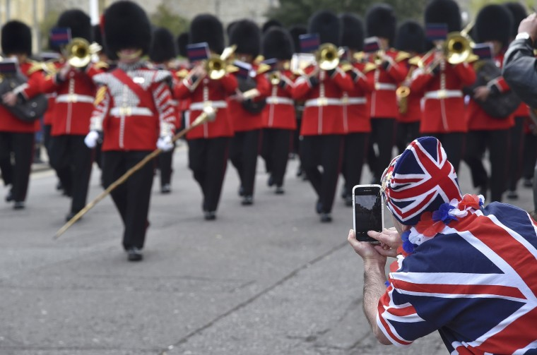 Image: A spectator takes photographs during the changing of the guard ceremony outside of Windsor Castle in Windsor Britain