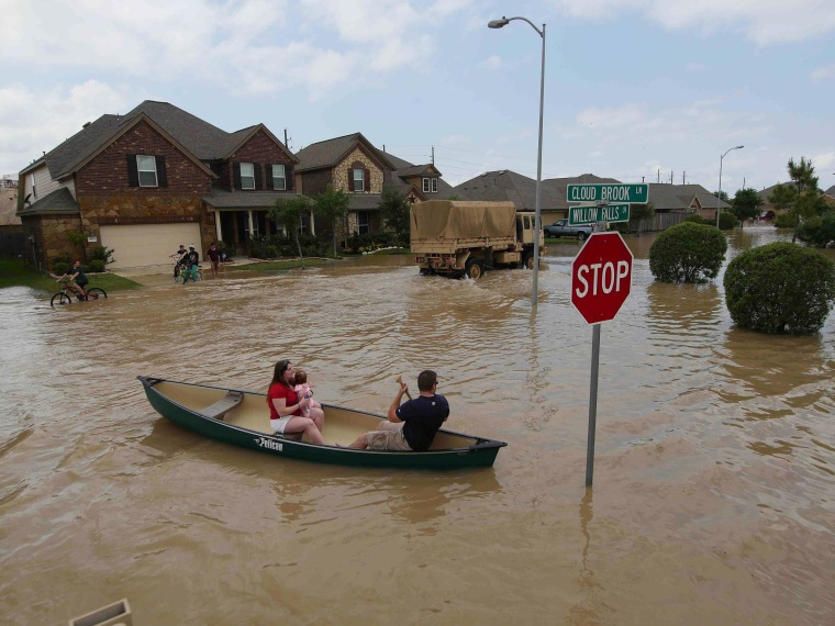 Image: A woman holds a baby in a canoe as Texas Guardsmen arrive to assist after flooding in Brookshire