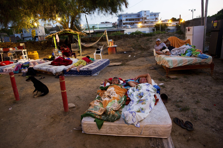 Image: People share a mattress as they sleep outside their collapsed homes