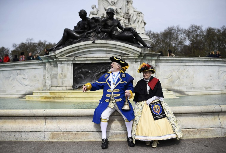 Image: Town Criers dressed in their traditional costumes watch the Changing of the Guard ceremony outside Buckingham Palace in London