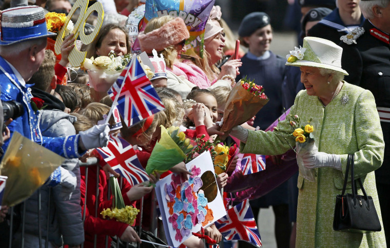 Image: Britain's Queen Elizabeth receives flowers and cards from well-wishers during a walk-about to celebrate her 90th birthday in Windsor