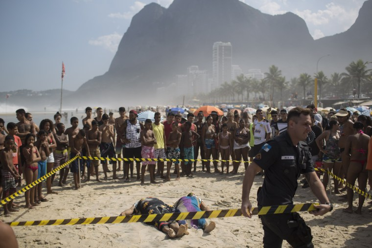 Image: A police officer tapes off the area around two people who were killed when a bike lane collapsed in Rio de Janeiro