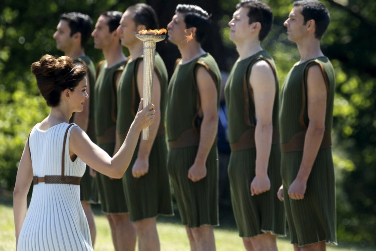 Image: Greek actress Katerina Lehou, playing the role of High Priestess, carries the Olympic flame past youths during the Olympic flame lighting ceremony