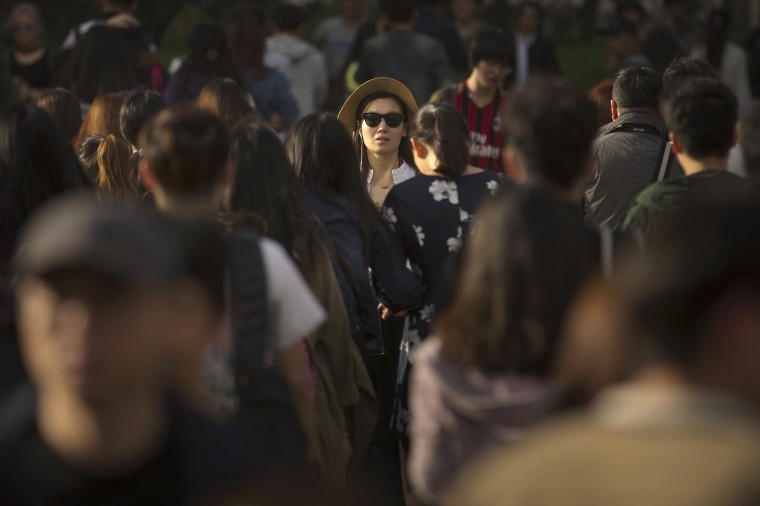 Image: A woman crosses a street at a busy intersection in central Beijing
