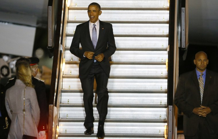 Image: U.S. President Barack Obama smiles as he walks down the steps of Air Force One on his arrival at Stansted Airport, England
