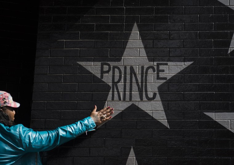 Image: A woman touches the Prince star on the wall outside First Avenue nightclub