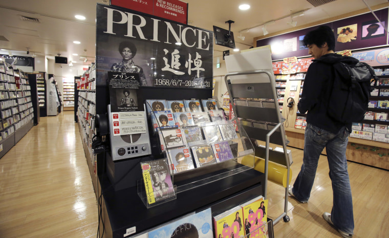 Image: A customer looks around a booth set up in memory of Prince at a music shop in Tokyo