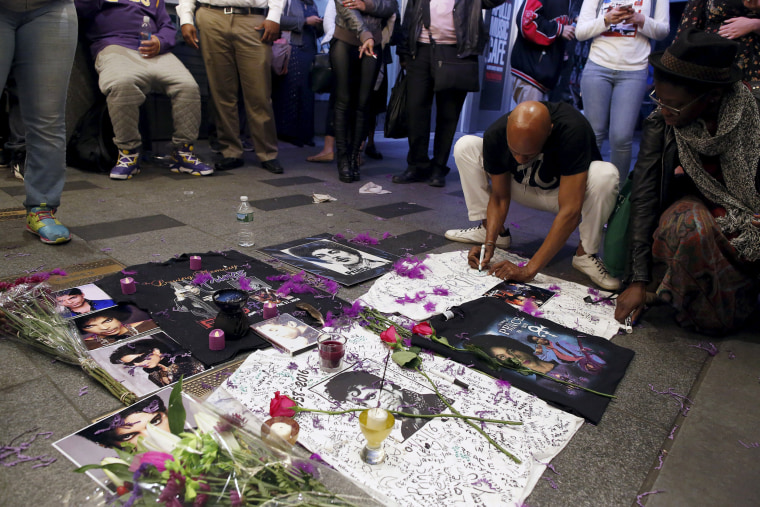 Image: A man writes on a makeshift memorial as fans gather at Harlem's Apollo Theater to celebrate the life of the deceased musician in New York