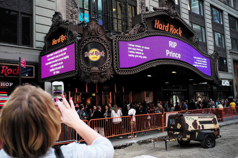 Image: A woman takes a picture of a tribute message in New York