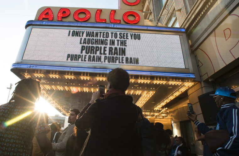 Image: People gather outside the Apollo Theater to listen to music by Prince in New York