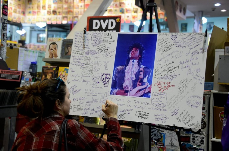 Image: A fan writes a message at a makeshift memorial at Amoeba Records in Hollywood, California