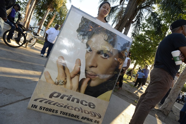 Image: A fan holds a poster of late musician during a gathering to pay tribute to his life and work in Los Angeles, California