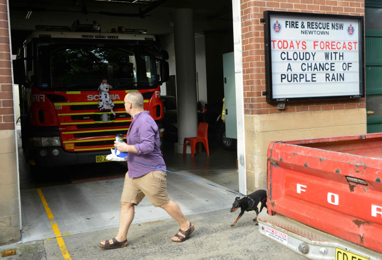 Image: A pedestrian walks past a fire station in Sydney with a tribute message displayed