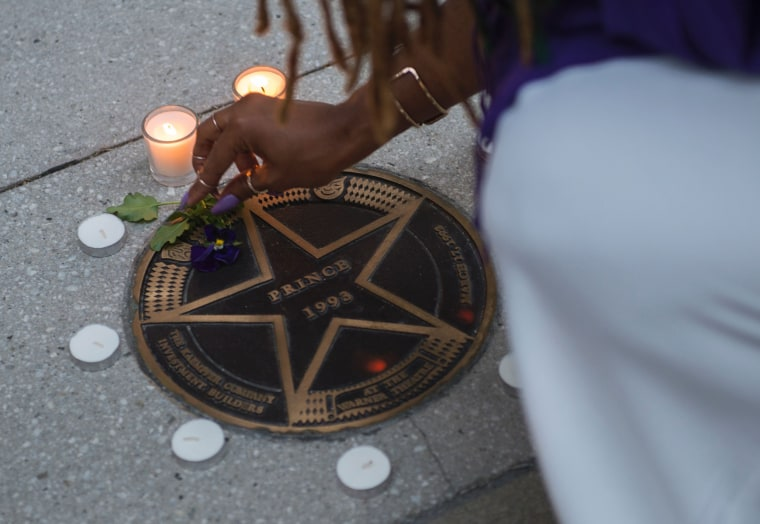 Image: A woman lights candles in remembrance to Prince around his star at the Warner Theater in Washington, D.C.