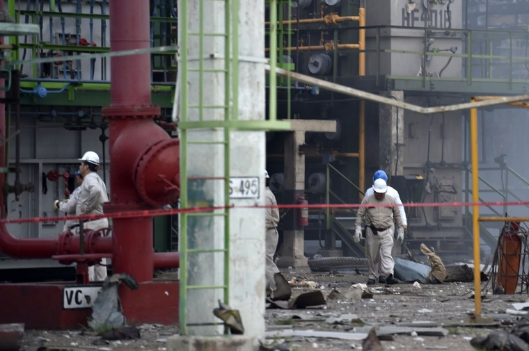 Image: Workers search for victims at the site of the blast