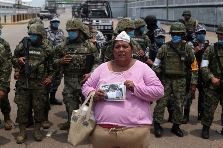 Image: Rosa Villalobos stands in front of  soldiers as she holds up a photo of her son