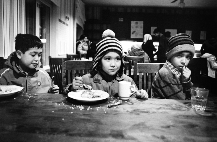 """""""He understands us,"""" Musaitif said as she cooked lunch and the photographer chatted with her children and husband. """"Because we lost our lives, we lost our country, we lost our children, we lost our parents."""" She insisted the photographer share the family's meal of fried greens and flat bread.  Above: Brothers Mahdi and Amir-Abbas from Afghanistan at lunch with their Iraqi friend Mahood in Nagu on December 30."""