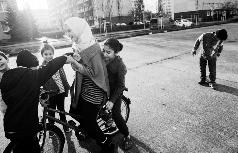"""""""You're taking somebody out of the context and if you have somebody in a refugee camp you've immediately labelled them as a refugee,"""" he said. """"By doing portraits of them this way, it's about the person.""""  Above: Iraqi, Syrian and Kurdish children play outside their hostel in Schonefeld, Berlin on Dec. 27."""