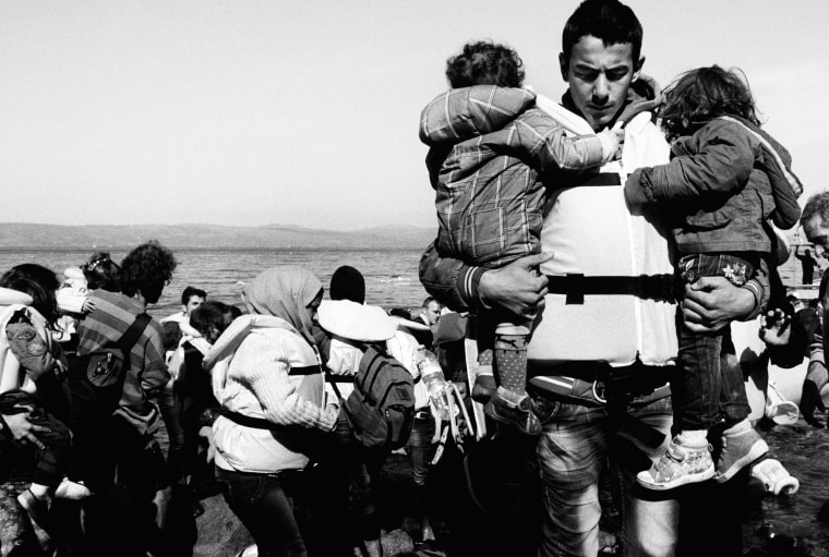 A father carries his two children from the boat after landing in Lesvos on Oct. 26.