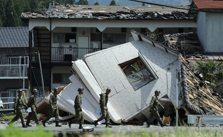 Image: Soldiers walk before a collapsed house to search for missing people in Minami-Aso