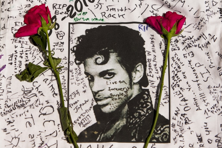 Image: Flowers lay on a T-shirt signed by fans of singer Prince