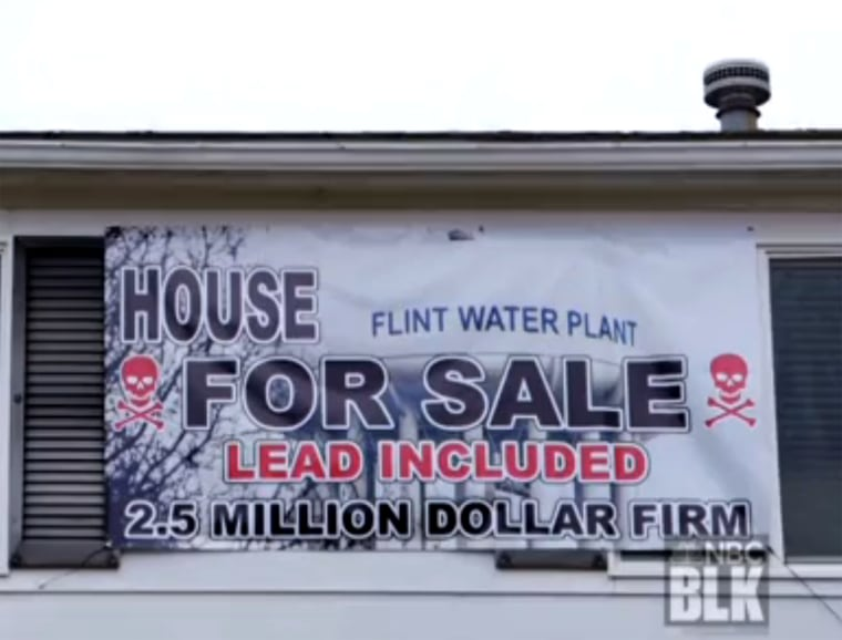 "In March, Estelle Holley bought a mock ""for sale"" sign decorated with a skull and bones and draped it across the front of her house."
