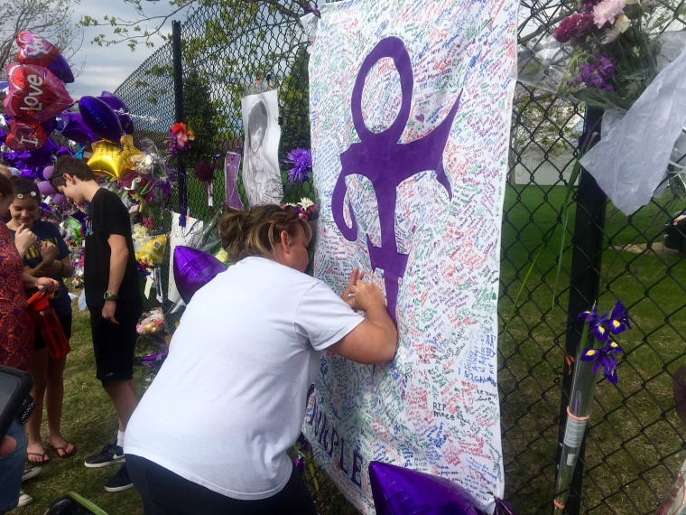 A woman writes on memorial sheet adorned with the symbol Prince once used to identify himself outside Paisley Park in Chanhassen, Minn., on April 23, 2016.