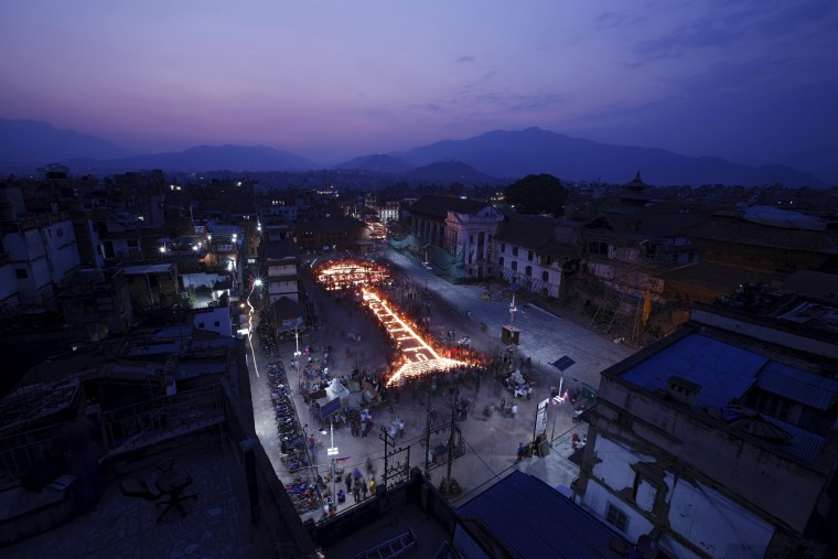 Image: Nepalese people lit candles to create the shape of historic nine-storey Dharara tower and Kasthamandap temple in Kathmandu