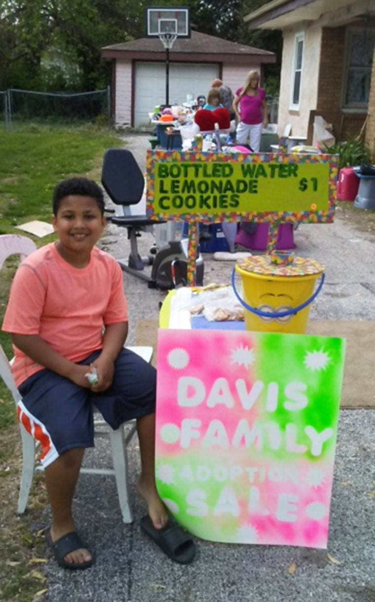 Tristan Jacobson selling lemonade at a yard sale to raise money to help the Davis family formally adopt him.