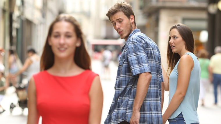 man walking with his girlfriend and looking amazed at another girl